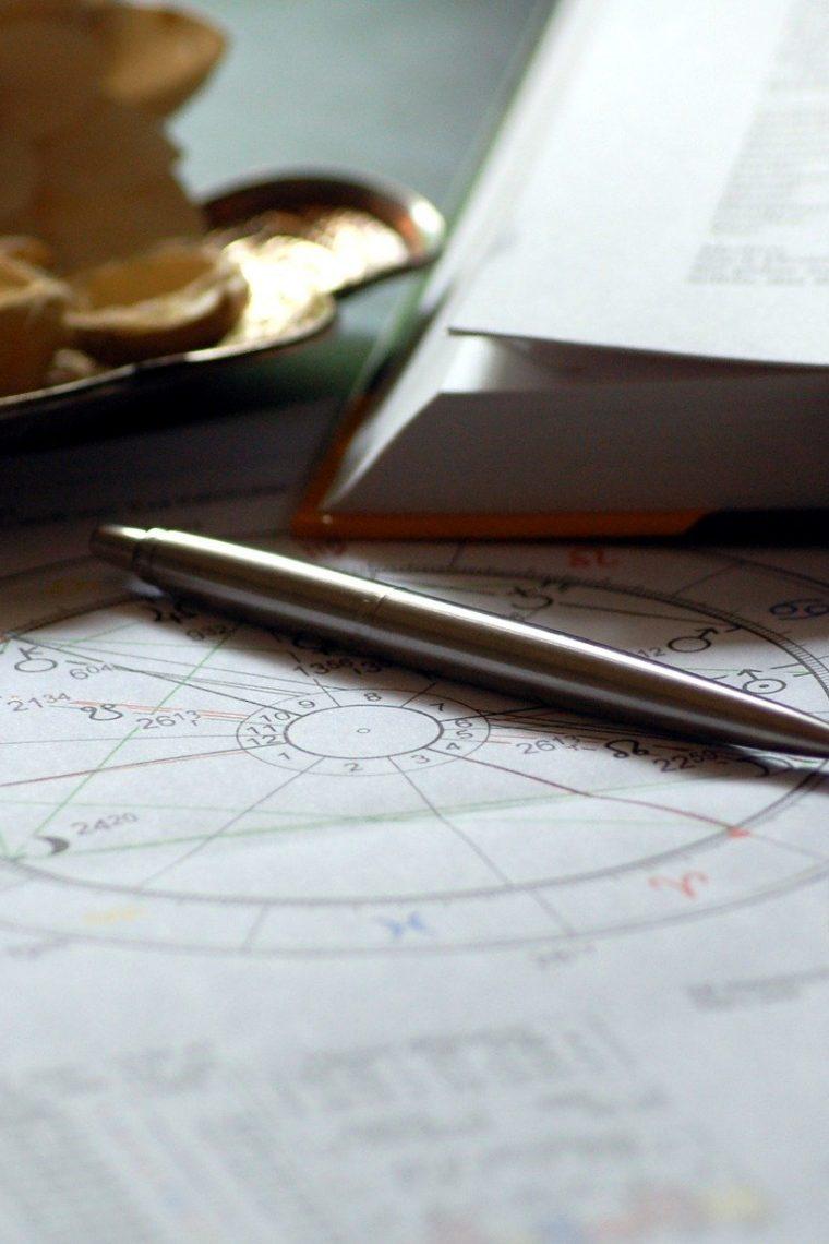 astrologický rádix na papieri, pero a otvorená kniha