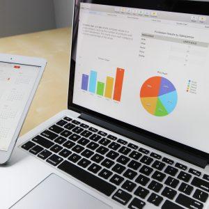 business - notebook s grafmi na obrazovke a mobil v ruke