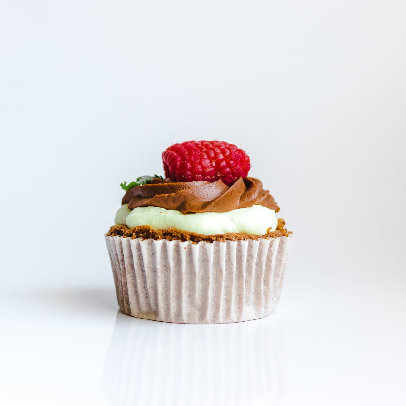 photograph of chocolate cupcake with red strawberry toppings