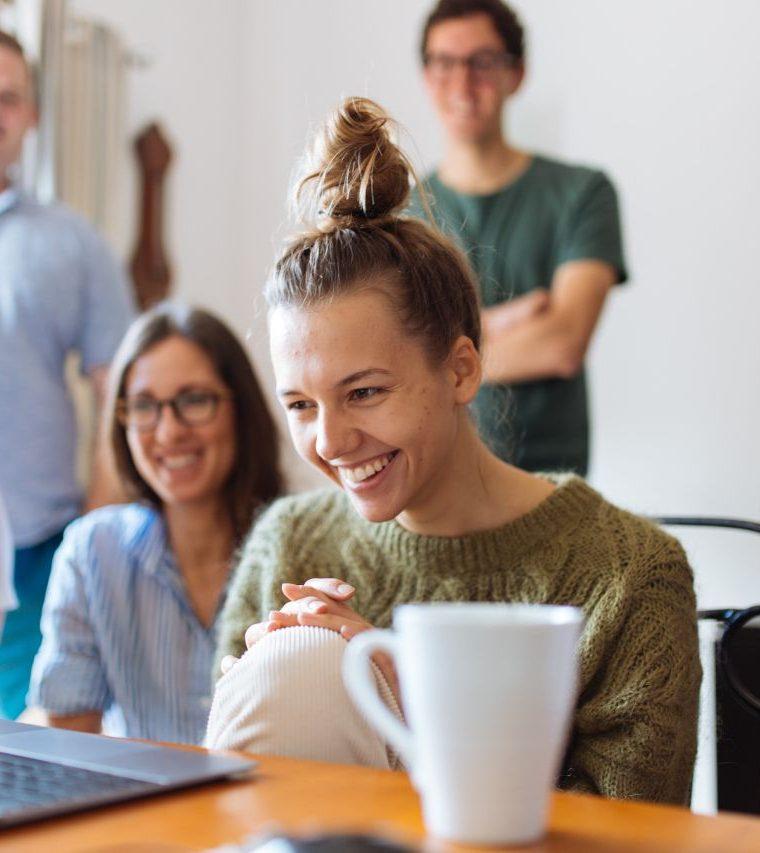 usmiata skupina ľudí nad pracovným stolom