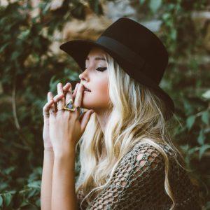 dievča s blond vlasmi v klobúku medituje