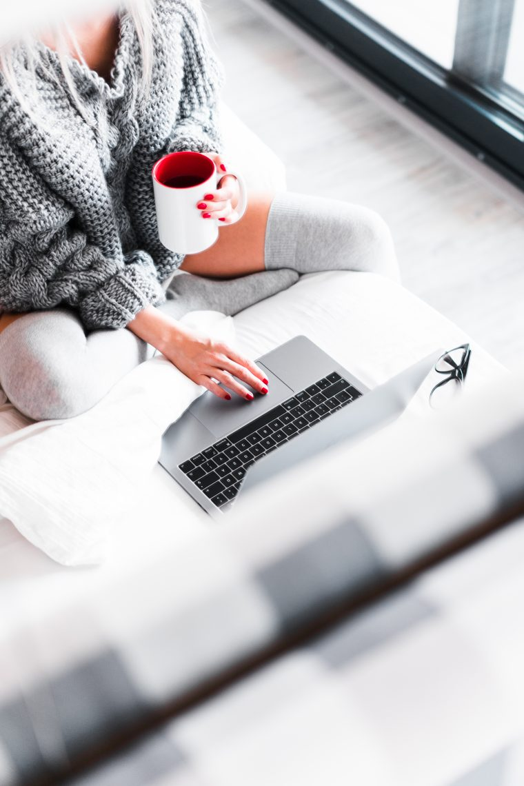 woman working from her bed with laptop